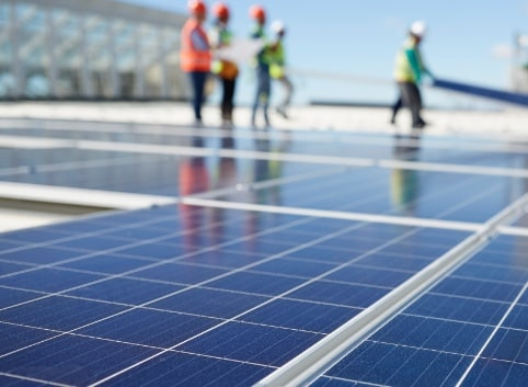 Workers on solar panel supporting sustainability.